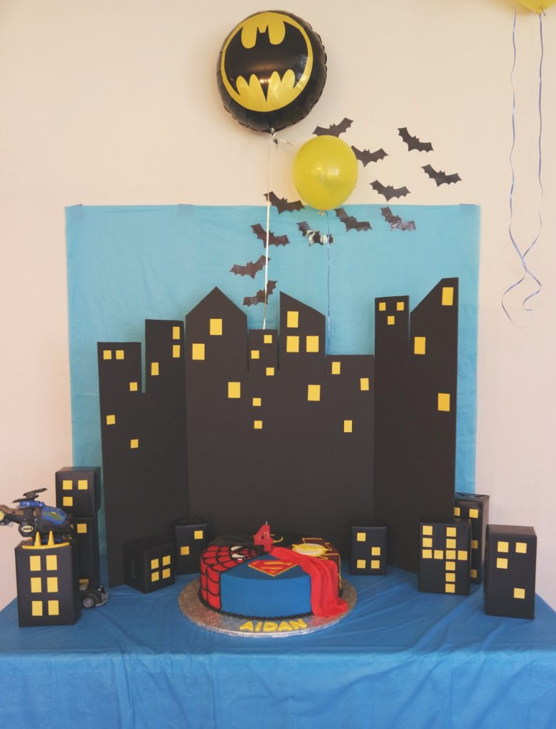 Superhero birthday cake and amazing Gotham City backdrop // Superhero Birthday Party Ideas - easy and fun superhero games and party decorations you can DIY, from a Gotham City backdrop to Captain America's shield toss #superhero #superherobirthday #superheroparty