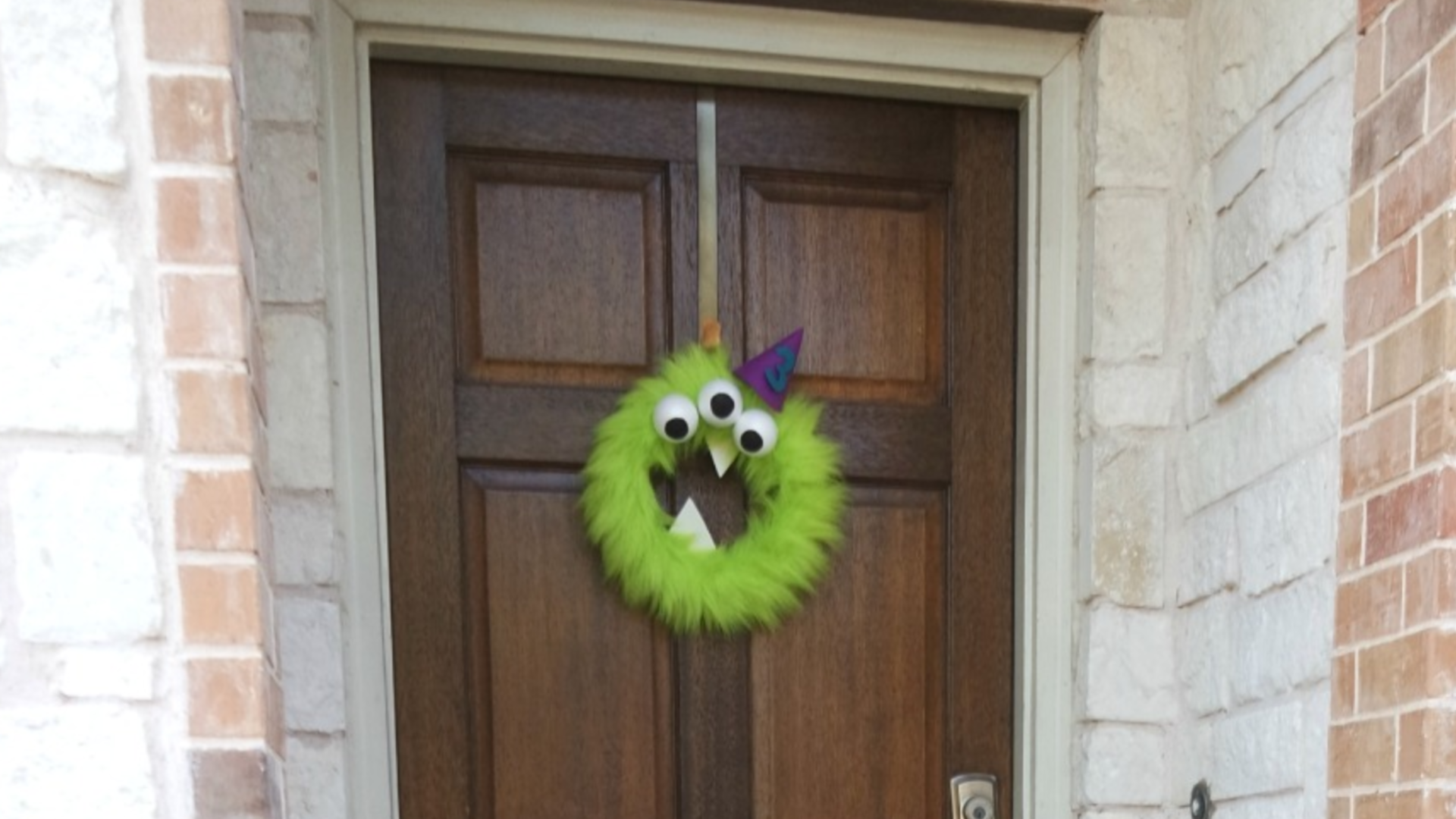This adorable furry monster wreath doubles as birthday AND Halloween decor. A quick and low-cost DIY addition to your monster birthday decorations. #monsterparty #monsterbirthday